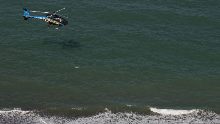 A state police helicopter searches the waters of the Gulf of California for survivors of a capsized fishing boat near San Felipe, Mexico, Monday, July 4, 2011. A U.S. tourist died after a fishing boat capsized in an unexpected storm in the Gulf of California off the Baja California peninsula and of the 44 people on the boat, seven U.S. tourists remain missing along with one Mexican crew member, the Mexican navy said. (AP Photo/Francisco Vega)