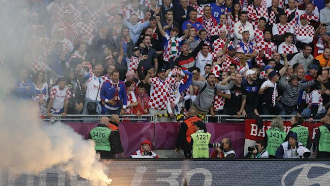 FILE - The June 14, 2012 file photo shows Croatian fans cheering after a flare was thrown onto the pitch during the Euro 2012 soccer championship Group C match between Italy and Croatia in Poznan, Poland. UEFA has charged the Croatian football federation with its fans' bad behavior.  (AP Photo/Anja Niedringhaus)