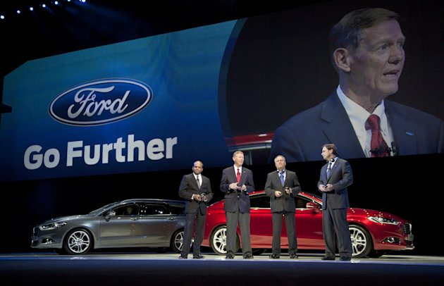 "With two new Ford Mondeo models seen in the background, Raj Nair, group vice President global product development, left, Alan Mulally, President and CEO of Ford Motor Company, center, Stephen Odel, chairman and CEO Ford Europe, and Jim Farley, group vice President global marketing, sales & service, from left to right, answer questions during a presentation of fresh Ford models in Amsterdam, Netherlands, Thursday Sept. 6, 2012. Ford has unveiled 15 new or restyled vehicles for the European market that it will launch over five years to revive sales. The refreshed lineup announced Thursday includes a second-generation Kuga midsize SUV to be launched this year, as well as a new Ecosport compact SUV and the European launch of the larger Edge. Ford also will launch the iconic Mustang in Europe. Ford Europe CEO Stephen Odell said improvements in the ""brutal"" European market are not expected soon. Ford, he said, is increasing its investment in Europe to be ready when the market bounces back. (AP Photo/Peter Dejong)"