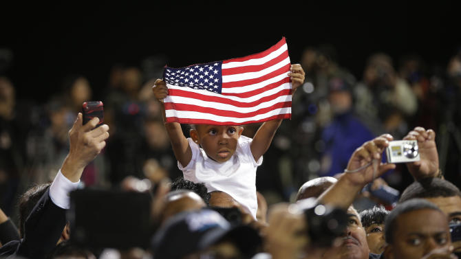 A young supporter holds up a U.S. flag during a campaign event for President Barack Obama at Doolittle Park, Wednesday, Oct. 24, 2012, in Las Vegas. (AP Photo/Pablo Martinez Monsivais)