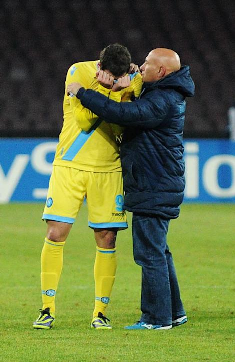 Napoli's Gonzalo Higuain is comforted by a team staffer as he walks off the pitch at the end of a Champions League, group F, soccer match between Napoli and Arsenal, at the Naples San Paolo stadiu