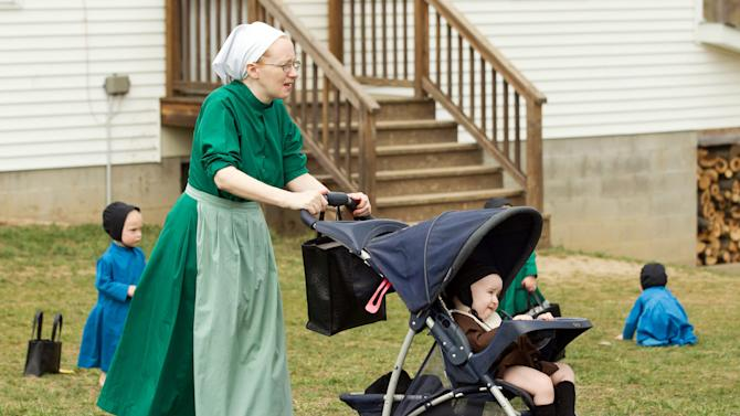 Emma Miller pushes her daughter in a stroller outside the school house in Bergholz, Ohio on Tuesday, April 9, 2013.  Miller is leaving for prison this week for her role in the hair and beard cutting scandal against other members of the Amish community.  (AP Photo/Scott R. Galvin)