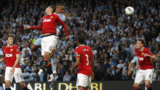 Manchester City's Vincent Kompany, 3rd left, scores against Manchester United during their English Premier League soccer match at The Etihad Stadium, Manchester, England, Monday, April 30, 2012. (AP Photo/Jon Super)