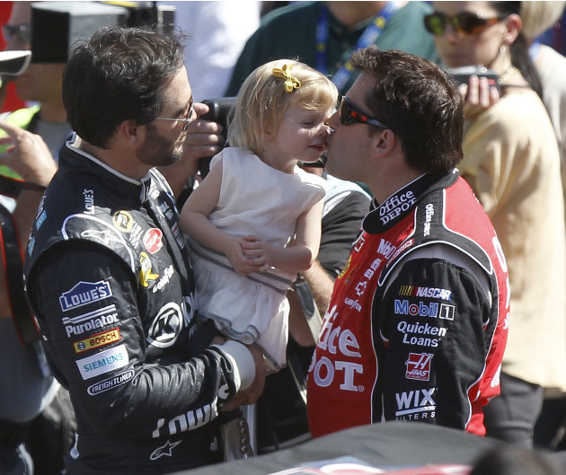 Jimmie Johnson, left, holds his daughter Genevieve, center, up as she gives a kiss to Tony Stewart before the NASCAR Sprint Cup Series auto race at Phoenix International Raceway on Sunday, March 4, 20