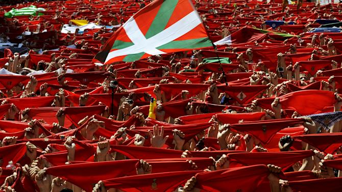 """A Basque flag known as the """"Ikurrina"""" flies alongside traditional red scarves held up by revellers during the start of the San Fermin festival in Pamplona"""