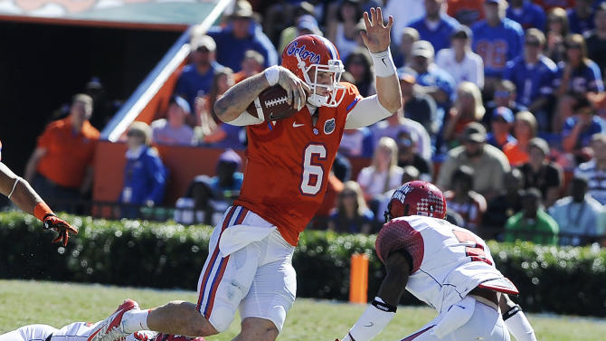 Florida quarterback Jeff Driskel (6) scampers to get away from Louisiana-Lafayette linebacker Justin Anderson (34) and  cornerback Jemarlous Moten (2) during the first half of an NCAA college football game in Gainesville, Fla., Nov. 10, 2012.  (AP Photo/Phil Sandlin