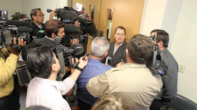 CORRECTS TO JUDGE HAMILTON, NOT COLLINS IN SECOND SENTENCE - Colleen and Boby Middleton, the parents of victim Robert Middleton, speak to the media after hearing regarding Don Willburn Collins at the 359th Judicial District Court with Judge Kathleen Hamilton on Thursday, March 6, 2014, in Conroe, Texas. Collins, now 28, accused of dousing Middleton with gasoline and setting him on fire in 1998 when he was a teenager, can be tried as an adult for murder after the victim died from his burns nearly 13 years later, Judge Hamilton ruled Thursday. (AP Photo/ The Courier, Jason Fochtman) MANDATORY CREDIT