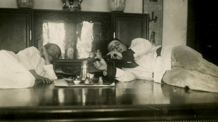 "In this photo taken in about 1930 released by American author Steven Martin, a young Westerner smokes opium by an Asian man in French Indochina. One Halloween night, in a blacked-out bedroom in Bangkok's Chinatown, Steven Martin went into physical and mental free fall. High fever oscillated with shivering cold, gut-wrenching stomach pains brought on waves of diarrhea. Howling in agony, he leapt around the room in a kind of devil dance, his body smeared with oily sweat, vomit, mucus and feces. ""Opium Fiend, A 21st Century Slave to a 19th Century Addiction''  opens with this harrowing description of the author trying to cut himself off from a drug that had taken over his life as a freelance journalist in Southeast Asia.  Although Martin doesn't advocate the use of opium,  his memoir is no simple cautionary tale, nor was he  your ordinary backpacker junkie, such as still roam this region of cheap and plentiful drugs. (AP Photo/Courtesy of Steven Martin) EDITORIAL USE ONLY, NO SALES"