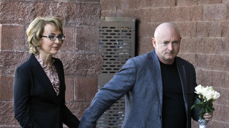 Former Rep. Gabrielle Giffords, left, and husband Mark Kelly, walk over to place flowers at the site of a memorial to the Tucson mass shooting victims, as they returned to the site of a shooting that left her critically wounded to urge key senators to support expanded background checks for gun purchases, Wednesday, March 6, 2013, in Tucson, Ariz. (AP Photo/Ross D. Franklin)