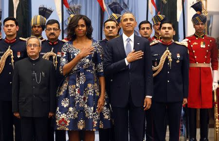 U.S. President Obama and first lady Michelle hold their hands over their hearts during the playing of the U.S. National Anthem with India's President Mukherjee at the Rashtrapati Bhavan presidential palace in New Delhi