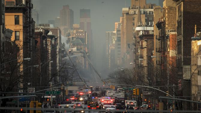 Firefighters and emergency personnel respond at the site of a residential apartment building which had collapsed and was engulfed in flames in New York City's East Village neighborhood