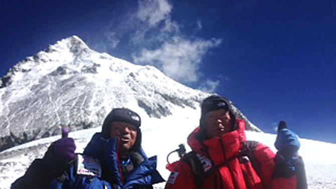 In this May 22, 2013 photo distributed by Miura Dolphins Co. Ltd., 80-year-old Japanese extreme skier Yuichiro Miura, right, and his son, Gota pose at their South Col camp at 8,000 meters (26,247 feet) before their departure for Camp 5 during their attempt to scale the summit of Mount Everest. Miura, who climbed Mount Everest five years ago, but just missed becoming the oldest man to reach the summit, was back on the mountain Wednesday to make another attempt at the title. (AP Photo/Miura Dolphins Co. Ltd.)  MANDATORY CREDIT