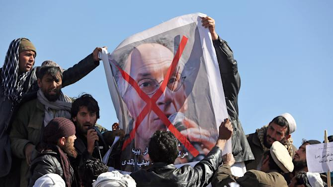 Afghans hold poster of French magazine Charlie Hebdo editor in chief, Gerard Briard, during a protest against caricatures published in the magazine in Kabul, Afghanistan, Tuesday, Jan. 27, 2015. Hundreds of people have demonstrated in the Afghan capital against the publishers of the French satirical magazine Charlie Hebdo, accusing them of blasphemy. (AP Photo/Rahmat Gul)