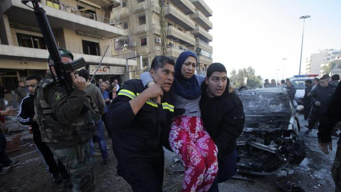 Civil defence members carry a wounded woman as a Lebanese Army soldier secures the area at the site of an explosion in Beirut