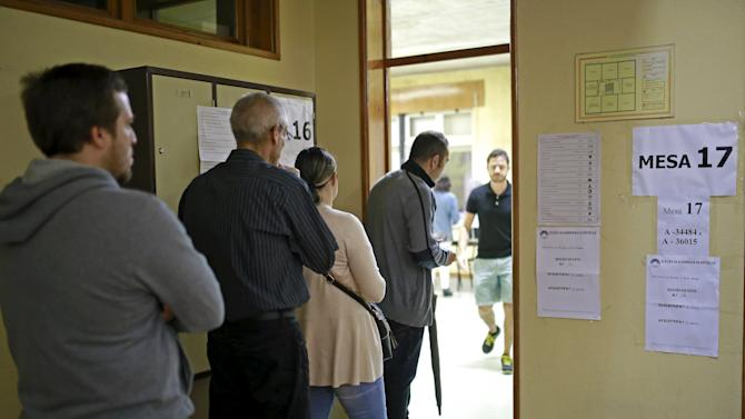 People waits to vote at a polling station during the general election in Massama