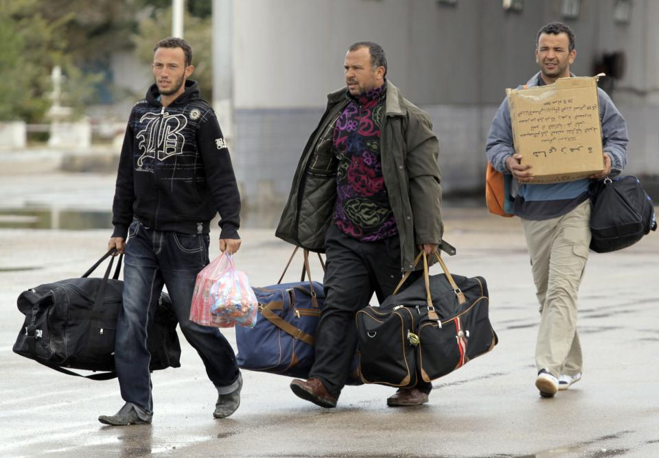 Tunisian men who fled from Libya carry their belongings at the Tunisia-Libyan border, near the town of Ben Guerdane,Tunisia, Wednesday, Feb. 23, 2011. (AP Photo/Lefteris Pitarakis)