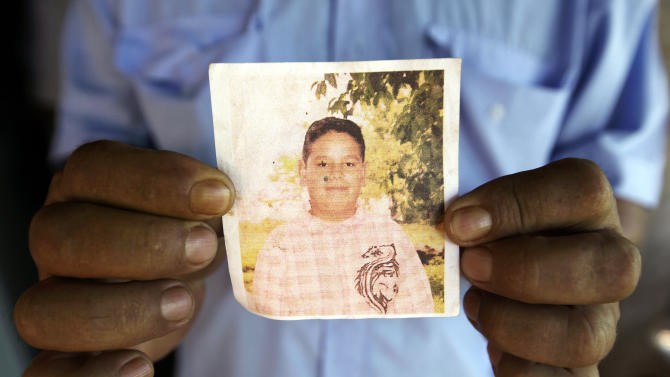 """In this Nov. 13, 2012 photo, Roberto Ortega holds a photocopy of a portrait of his only son Luciano in the Yvy Pyta settlement near Curuguaty, Paraguay.  Luciano, 18, died during the """"Massacre of Curuguaty"""" on June 15 when negotiations between farmers occupying a rich politician's land ended with a barrage of bullets that killed 11 farmers and 6 police officers. Ortega had sold his tiny shack and plot of land to a neighbor and marched onto the ranch with his wife, carrying all their remaining possessions. (AP Photo/Jorge Saenz)"""