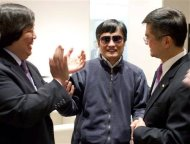 A handout photo from US Embassy Beijing Press office shows blind activist Chen shaking hands with U.S. Ambassador to China Locke, in Beijing