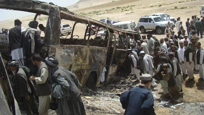 Afghan men surround a burned bus after it collided with the wreckage of a truck that was attacked by Taliban insurgents in Maiwand district, on the highway between Kandahar and Helmand, Afghanistan, Friday, April 26, 2013. Scores of people aboard the bus were killed in the fiery crash, officials said. (AP Photo/Abdul Khaliq Kandahari)