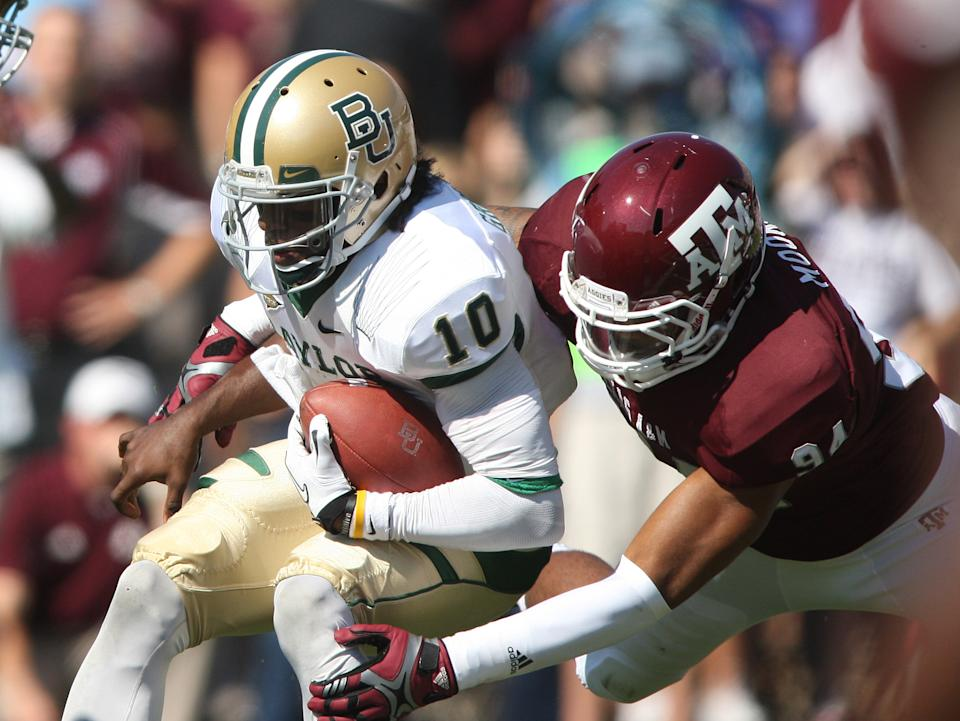 Texas A&M's Damontre Moore (94) sacks Baylor's Robert Griffin III during the first half of an NCAA college football game Saturday, Oct. 15, 2011, in College Station, Texas. (AP Photo/Jon Eilts)
