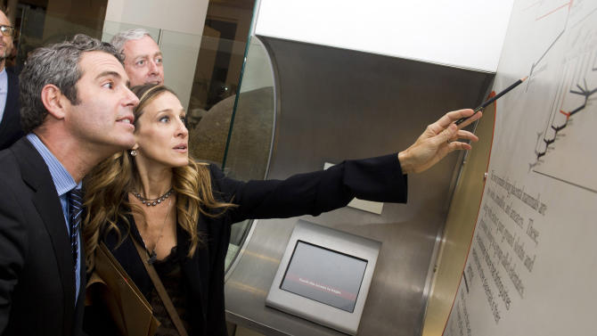 """Andy Cohen, left, and Sarah Jessica Parker search for clues at the Friends In Deed's """"A Little Jurassic Treasure Hunt"""" held a the American Museum of Natural History, in New York, Monday, Oct. 3, 2011. The hunt devised by composer Stephen Sondheim prompted hundreds of people to scamper through the dinosaur section of the American Museum of Natural History as part of a charity gala. (AP Photo/Charles Sykes)"""