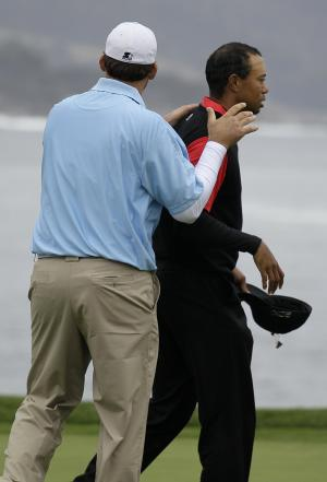 Dallas Cowboys quarterback Tony Romo, left, puts his hands on the shoulders of Tiger Woods on the 18th green at Pebble Beach Golf Links during the final round of the AT&T Pebble Beach National Pro-Am golf tournament in Pebble Beach, Calif., Sunday, Feb. 12, 2012. (AP Photo/Eric Risberg)