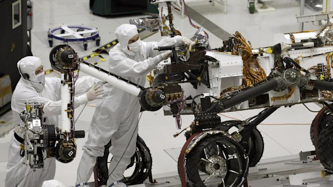 FILE - This Sept. 16, 2010 file photo shows engineers working on the Mars rover Curiosity at NASA's Jet Propulsion Laboratory in Pasadena, Calif. After traveling 8 1/2 months and 352 million miles, Curiosity will attempt a landing on Mars the night of Aug. 5, 2012. (AP Photo/Jae C. Hong, file)
