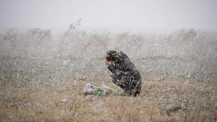 A woman prays for the deceased of March 11, 2011 earthquake and tsunami at a place where she was employed at a photo studio at the time, in Rikuzentakata, Iwate prefecture
