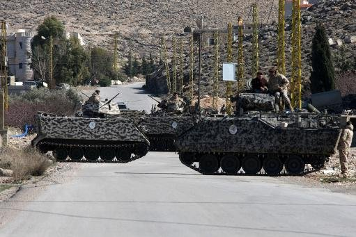 Lebanese soldiers are deployed on a road at the entrance of the village of Arsal, on the border with Syria, on February 2, 2013