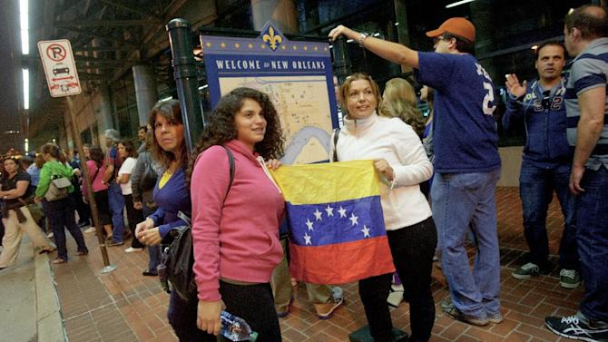 Mailyn Yoria, 19, and her mother Yelby Yoria of Miami, smile as they pose for a picture holding a Venezuelan flag as they wait in line to vote at the New Orleans Ernest Morial Convention Center, in New Orleans, Sunday, Oct. 7, 2012. Hundreds of Venezuelans living in the U.S. streamed into New Orleans on Sunday to cast ballots in the presidential election in their homeland, many of them determined to end the 13-year reign of Hugo Chavez. With the country's consulate in Miami closed, thousands of Venezuelans traveled by bus, car and plane to cast their votes at the consulate in New Orleans. (AP Photo/Matthew Hinton)