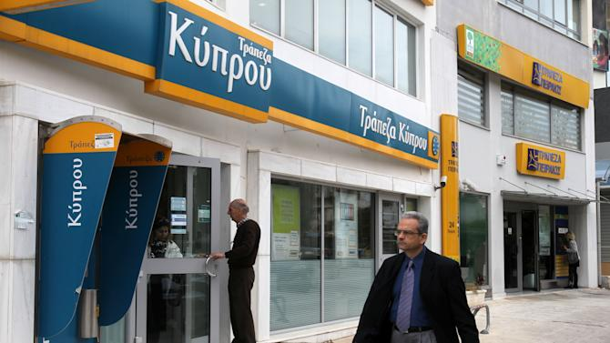 Customers enter a Bank of Cyprus branch as a Piraeus Bank branch is seen in the background in Athens, Wednesday, March 27, 2013. Greece's Piraeus Bank reached an agreement Tuesday to buy the Greek operations of three Cypriot banks for euro 524 million ($678 million). Piraeus Bank said Cypriot bank branches in Greece re-open Wednesday, a day earlier than in Cyprus. (AP Photo/Thanassis Stavrakis)