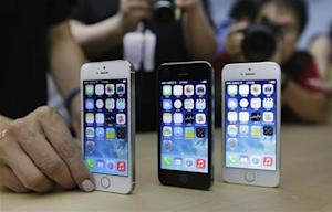 A staff member sets up the new iPhone 5Ss for display picture at Apple Inc's announcement event in Beijing