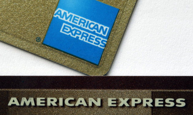 FILE-In this Tuesday, Jan. 17, 2012 file photo, two American Express cards are shown in Surfside, Fla. American Express is paying $112.5 million in refunds and fines to settle regulators' accusations that it charged illegal late fees and deceived customers to pressure them to pay off old debts or buy extra credit card services. (AP Photo/Wilfredo Lee, File)