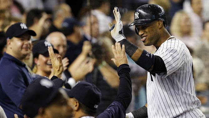 New York Yankees' Robinson Cano is greeted at the dugout steps after hitting a fifth-inning, two-run home run against the Boston Red Sox during their baseball game at Yankee Stadium in New York, Wednesday, Oct. 3, 2012. (AP Photo/Kathy Willens)