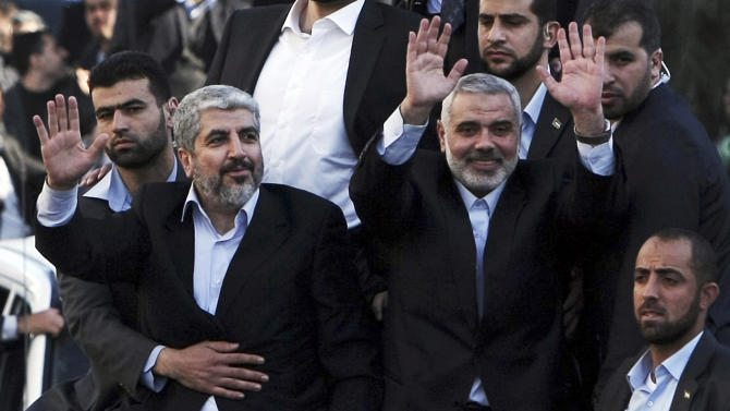 The exiled Hamas chief Khaled Mashaal, left, and Gaza's Hamas Prime Minister Ismail Haniyeh wave from the rooftop of a vehicle during a parade following Meshaal's arrival in Gaza City, Friday, Dec. 7, 2012. Mashaal, broke into tears Friday as he arrived in the Gaza Strip for his first-ever visit, a landmark trip reflecting his militant group's growing international acceptance and its defiance of Israel. Khaled Mashaal, who left the West Bank as a child and leads the Islamic militant movement from Qatar, crossed the Egyptian border, kissed the ground, and was greeted by a crowd of Hamas officials and representatives of Hamas' rival Fatah party.  (AP Photo/Mahmud Hams, Pool)