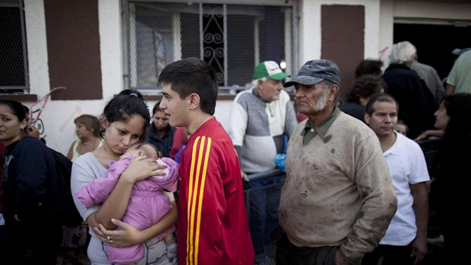 People affected by flooding line up to get help from the Red Cross in La Plata, in Argentina's Buenos Aires province, Thursday, April 4, 2013. Buenos Aires Gov. Daniel Scioli says 49 people died in this flooded capital of Argentina's largest province as torrential rains swamped entire neighborhoods, washing away cars and flooding some houses to their rooftops. The overall death toll is now 55, and more than 20 people are missing. (AP Photo/Natacha Pisarenko)