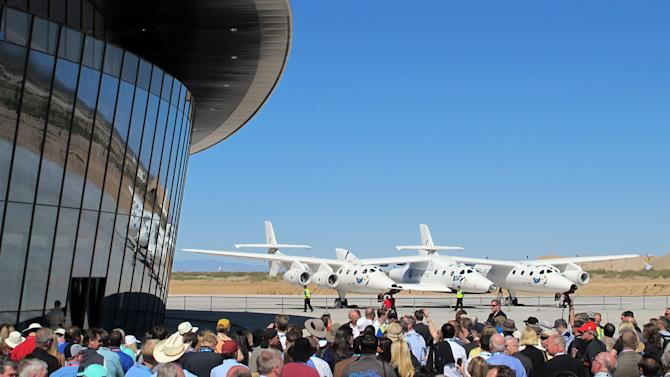 This Oct. 17, 2011 image shows a crowd gathered outside Spaceport America for a dedication ceremony as Virgin Galactic's mothership WhiteKnightTwo sits on the tarmac near Upham, N.M. More than 450 people from 46 countries have paid deposits to take suborbital flights with Virgin Galactic from the spaceport once powered test flights are completed and the company is licensed by the Federal Aviation Administration. (AP Photo/Susan Montoya Bryan)