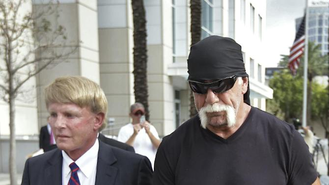 "Reality TV star and former pro wrestler Hulk Hogan, right, whose real name is Terry Bollea, leaves the United States Courthouse with his attorney David Houston after a news conference Monday, Oct. 15, 2012 Tampa, Fla. Hogan says he was secretly taped six years ago having sex with the ex-wife of DJ Bubba ""The Love Sponge"" Clem. Portions of the video of Hogan and Heather Clem were posted on the online gossip site Gawker. (AP Photo/Chris O'Meara)"