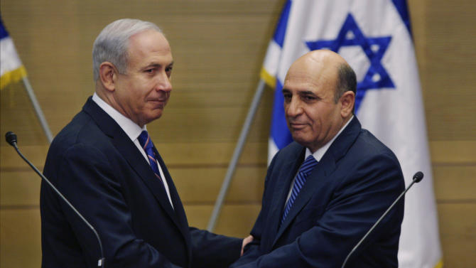 """Israel's Prime Minister Benjamin Netanyahu, left, and Kadima party leader Shaul Mofaz shake hands before holding a joint press conference announcing the new coalition government in Jerusalem, Tuesday, May 8, 2012. Netanyahu said Tuesday his new coalition government will promote a """"responsible"""" peace process with the Palestinians. (AP Photo/Sebastian Scheiner)"""