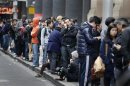 People queue outside an Apple store as they wait to buy an iPhone 5, in central Sydney