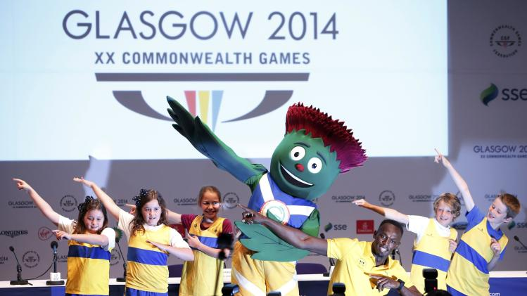 Jamaica's Usain Bolt poses with children before his news conference at the 2014 Commonwealth Games in Glasgow
