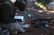 In this Thursday, Nov. 15, 2012 file photo, a Syrian rebel reads Quran during clashes with government forces in Aleppo, Syria. Through mid-2012, rebel power grew and Assad&#39;s army ramped up its response. Relentless government shelling leveled neighborhoods and killed hundreds. Regular reports emerged of mass killings by the regime or thugs loyal to it, pushing more Syrians toward armed struggle. The government, which considers the opposition terrorist gangs backed by foreign powers, denied any role, and does not respond to requests for comment on its military. The rebels, too, were accused of atrocities. (AP Photo/ Khalil Hamra, File)