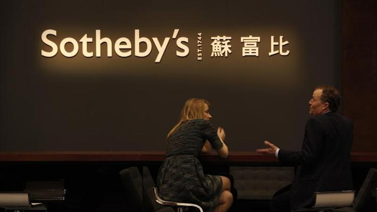 Staff members chat during Sotheby's preview in Hong Kong