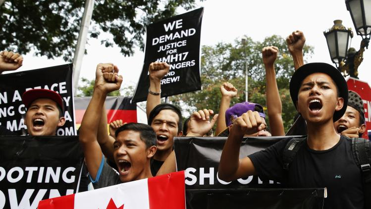 Protesters chant slogans demanding justice for victims of Malaysia Airlines Flight MH17 as they follow lead of organisers of rally held by UMNO's youth wing outside Russian embassy in Kuala Lumpur
