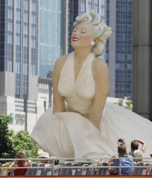 FILE - In this July 15, 2011 file photo, tourists on a double decker bus photograph Seward Johnson's 26-foot-tall sculpture of Marilyn Monroe, in her most famous wind-blown pose, on Michigan Avenue, in Chicago. (AP Photo/Charles Rex Arbogast, File)