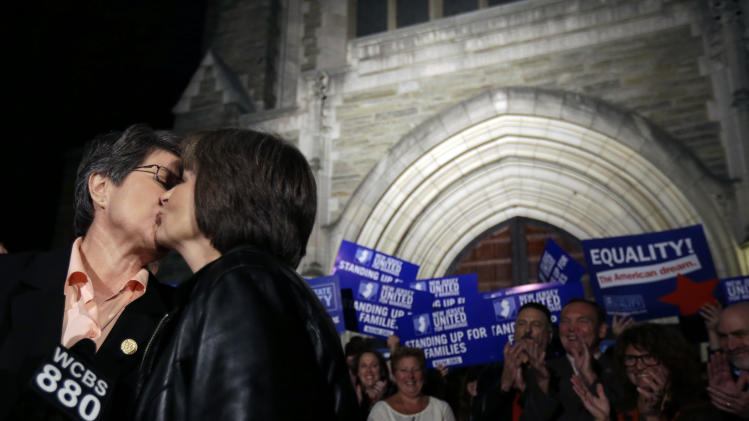 FILE - In this Sept. 27, 2013 file photo, Cindy Meneghin, left, kisses her partner Maureen Kilian, both from Butler, N.J., during a news conference at Garden State Equality in Montclair, N.J., hours after a Superior Court Judge ruled that New Jersey is unconstitutionally denying federal benefits to gay couples and must allow them to marry. Judge Mary Jacobson on Thursday, Oct. 10, 2013 refused to delay the start of same-sex marriage in New Jersey until a legal appeal can be settled. But the administration of Republican Gov. Chris Christie immediately sought and was granted a request to file an emergency challenge to the decision. (AP Photo/Julio Cortez, File)