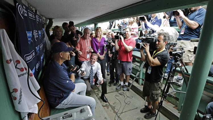 Cleveland Indians manager Terry Francona, left, is surrounded by members of the media in the visitor's dugout before a baseball game against the Boston Red Sox at Fenway Park in Boston, Thursday, May 23, 2013. Francona was Red Sox manager for the 2004 and 2007 World Series Championship seasons. (AP Photo/Charles Krupa)