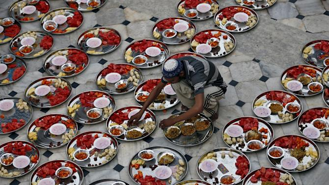 A Muslim man prepares plates of food for an Iftar meal inside a mosque in Ahmedabad