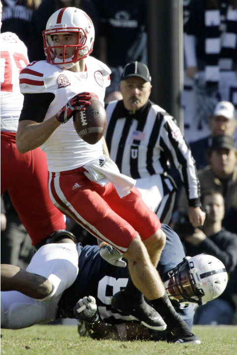Nebraska quarterback Taylor Martinez (3) spins away from Penn State defensive end Jack Crawford (81) during the second quarter of an NCAA college football game in State College, Pa., Saturday, Nov. 12