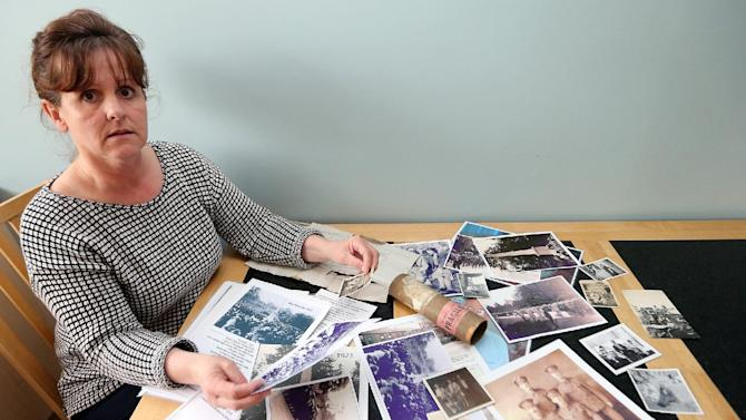 """In this May 7, 2014 photo, Amanda Nelson, the granddaughter of World War I Pvt. Wilfred Smith shows family photographs during an interview at her home in Barnard Castle, England. Nelson said that she made a special point of seeing the Steven Spielberg film """"Saving Private Ryan"""". The 1998 Oscar-winning film which depicts the fictional account of a WWII rescue mission for a single American soldier whose brothers have been killed in fighting. (AP Photo/Scott Heppell)"""
